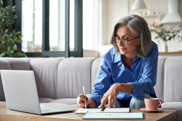 Stylish mature older woman working from home on laptop taking notes